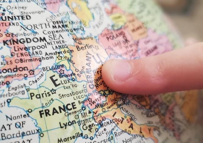 Finger pointing to Europe on a globe