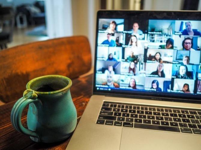 A coffee mug and a laptop with a video conference on.