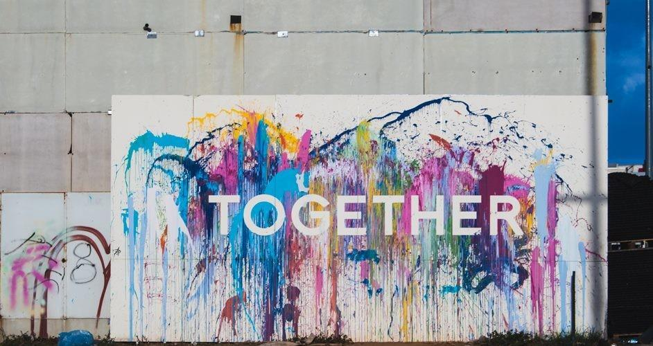 """The word """"Together"""" painted in a grey wall with bright colours."""